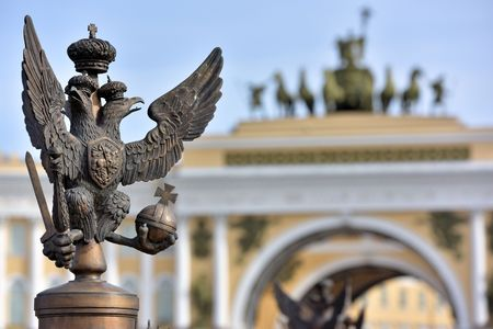 double headed eagle: Details of fence decoration with Russian Imperial Symbol of Double Headed Eagle at the Palace Square and behind blured view of the Triumphal Arches of the General Staff of St. Petersburg Russia Stock Photo