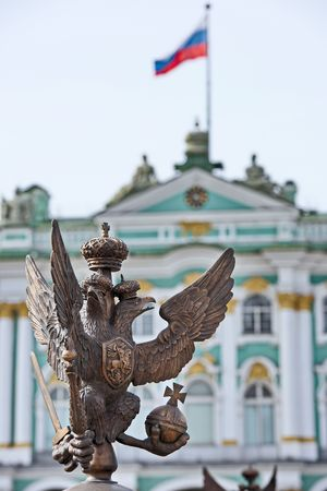 double headed eagle: Details of fence decoration with Russian Imperial Symbol of Double Headed Eagle Flag at the Palace Square and the Russian view on Hermitage at blured behind St. Petersburg Russia Editorial