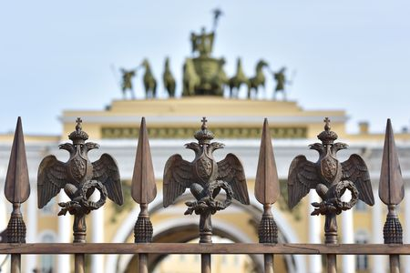 double headed eagle: Details of fence decoration with Russian Imperial Symbol of Double Headed Eagle at Palace Square behind blured view of gate to Palace Square in St. Petersburg Russia