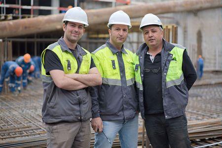 ingeniero civil: Dos ingeniero civil y un capataz mayor en sitio de construcci�n est�n inspeccionando las obras de construcci�n en curso.