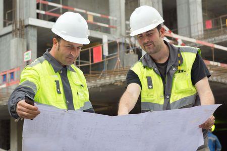 obreros trabajando: Ingenieros Civiles en el sitio de la construcci�n est�n inspeccionando la producci�n en curso de acuerdo a los planos de dise�o.