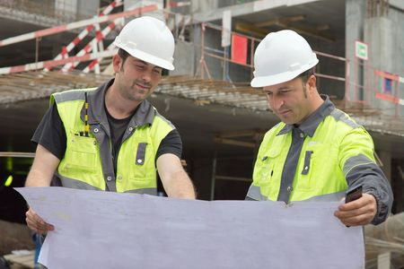 according: Civil Engineers at construction site are inspecting ongoing production according to design drawings.