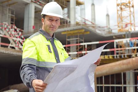 ingeniero civil: Ingeniero Civil en la obra de construcci�n est� inspeccionando la producci�n en curso de acuerdo a los planos de dise�o.