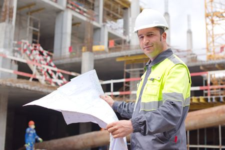 Civil Engineer at construction site is inspecting ongoing production according to design drawings. Stock Photo - 41906608