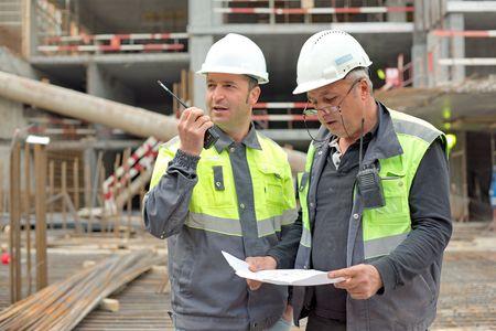edificio industrial: Ingeniero Civil y Senior Capataz en el emplazamiento de la obra están inspeccionando la producción en curso según el dibujo del diseño.