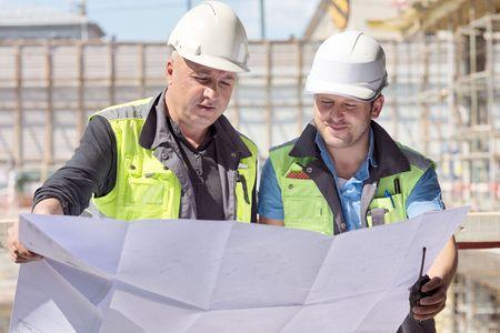 constructor: Ingeniero Civil y Senior Capataz en el emplazamiento de la obra están inspeccionando la producción en curso de acuerdo a los planos de diseño.