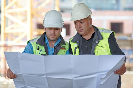 construction site: Civil Engineer And Senior Foreman at construction site are inspecting ongoing production according to design drawings.