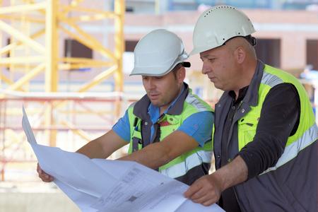 ingeniero civil: Ingeniero Civil y Senior Foreman en el sitio de la construcci�n est�n inspeccionando la producci�n en curso de acuerdo a los planos de dise�o.