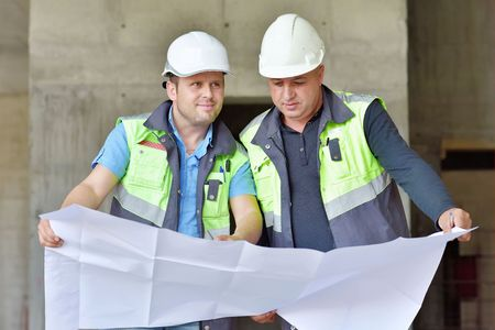 construction project: Civil Engineer And Senior Foreman at construction site are inspecting ongoing production according to design drawings.