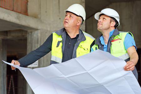 ingenieria industrial: Ingeniero Civil y Senior Foreman en el sitio de la construcción están inspeccionando la producción en curso de acuerdo a los planos de diseño.