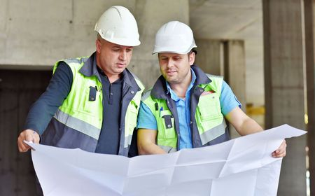 engineering design: Civil Engineer at construction site is inspecting ongoing production according to design drawings.