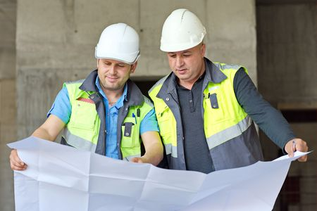 building work: Civil Engineers at construction site are inspecting ongoing production according to design drawings.