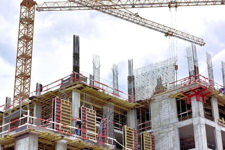 anuncio publicitario: Un nuevo edificio se está construyendo con el uso de la grúa torre