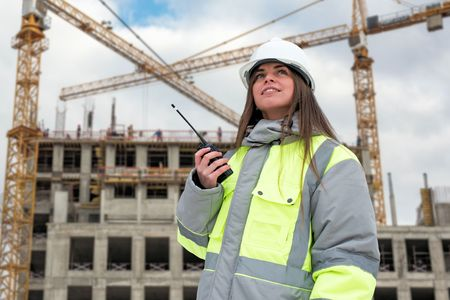 women: Civil Engineer at construction site is inspecting ongoing production according to design drawings.