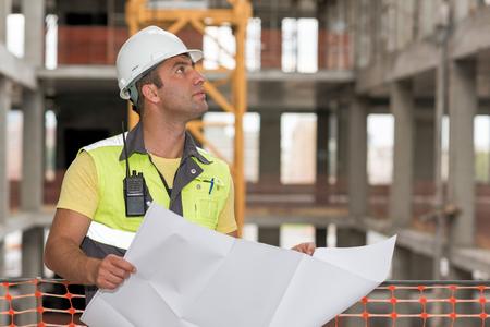 cantieri edili: Ingegnere Civile in cantiere sta ispezionando produzione in corso in base ai disegni di progetto.
