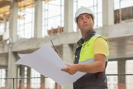 industrial industry: Civil Engineer at construction site is inspecting ongoing production according to design drawings.