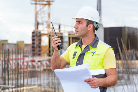 civil construction: Civil Engineer at construction site is inspecting ongoing production according to design drawings.