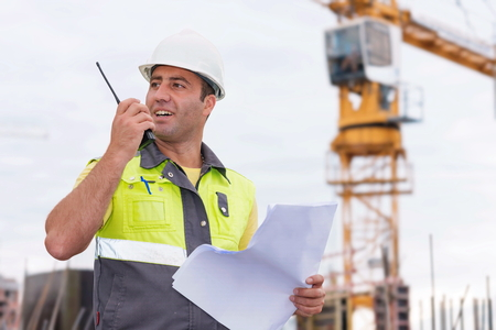 site manager: Civil Engineer at construction site is inspecting ongoing production according to design drawings.