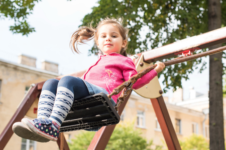 swing: Happy little girl is swinging at playground. Stock Photo