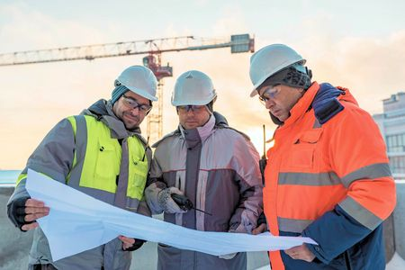 ingeniero civil: J�venes ingenieros civiles y capataz mayor en el emplazamiento de la obra est�n inspeccionando la producci�n continua de acuerdo con los planos de dise�o.