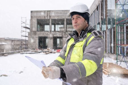 ongoing: Civil Engineer at construction site is inspecting ongoing production according to design drawings in difficult winter conditions. Stock Photo