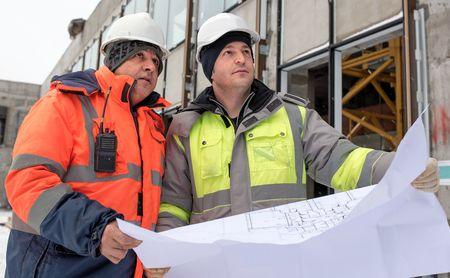 ingeniero civil: Ingeniero Civil y Senior Capataz en el emplazamiento de la obra est�n inspeccionando la producci�n continua de acuerdo con los planos de dise�o. Foto de archivo