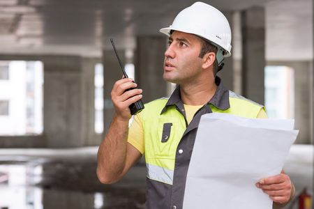 according: Civil Engineer at construction site is inspecting ongoing production according to design drawings.