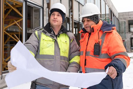 according: Civil Engineer And Senior Foreman at construction site are inspecting ongoing production according to design drawings.
