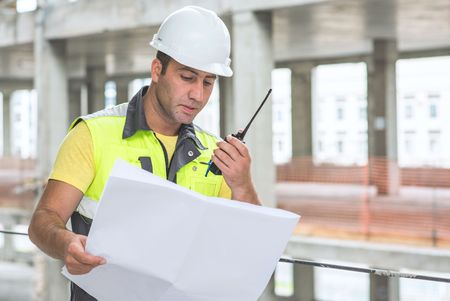 ongoing: Civil Engineer at construction site is inspecting ongoing production according to design drawings.