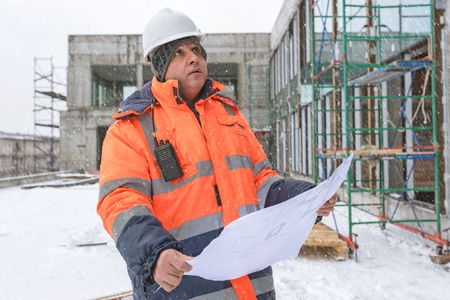 Senior Foreman At Construction Site is inspecting ongoing production according to design drawings in difficult winter conditions.