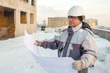 ingeniero civil: Ingeniero Civil en la obra de construcci�n est� inspeccionando la producci�n en curso de acuerdo a los planos de dise�o en invierno.