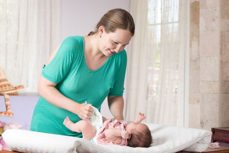 changing diaper: Mother is changing diaper of her daughter.