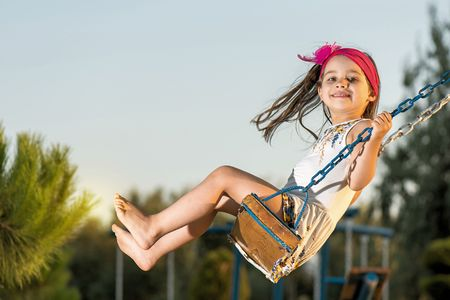 Little girl is swinging at play ground when sun is setting. Stock Photo
