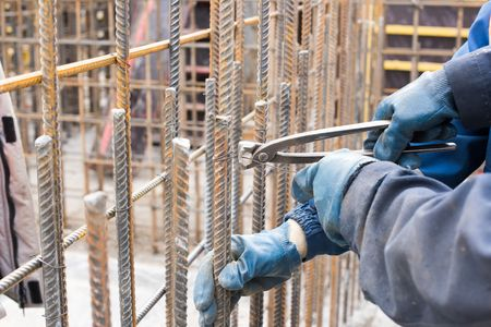 reinforcement: Worker at construction site is preparing reinforcement cage.