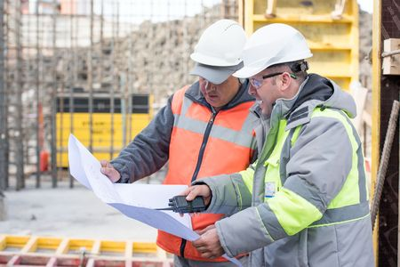 Civil engineer And Foreman at construction site are inspecting ongoing works according to design drawings. Standard-Bild