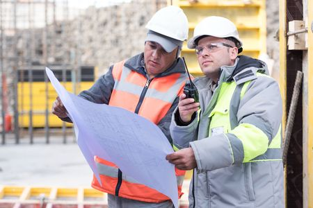 ongoing: Civil engineer And Foreman at construction site are inspecting ongoing works according to design drawings. Stock Photo