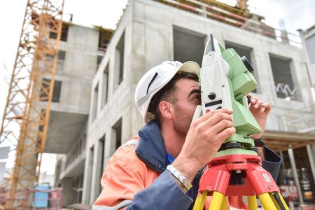 theodolite: Surveyor at at construction site is inspecting ongoing production Stock Photo