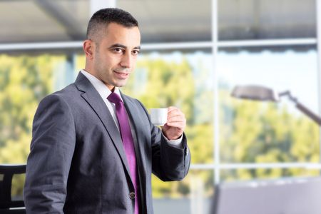 coffe break: Young And Confident Businessman Having Coffe Break In His Office