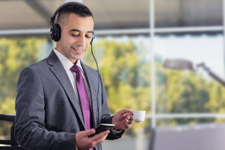coffe break: Young And Confident Businessman Having Coffe Break And Listening To Music In His Office