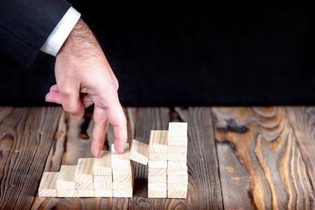 Businessman Walking Up Trappy Staircase Of Wooden Blocks To Success, Career In Business Concept