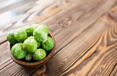 Brussel Sprouts In Wooden Bowl On Wooden Desk