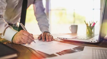 Homme d'affaires signant un document officiel au bureau Banque d'images - 77822370