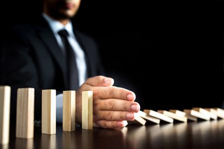 비즈니스 개념에서 체인 반응, 또는 시키거나 도미노를 방지하는 사업가 소박한 나무 책상에 지속적으로 전복
