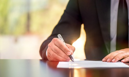 Businessman Is Signing A Legal Document In Office Stock Photo
