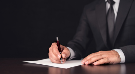 Businessman Writing A Legal Document Stock Photo