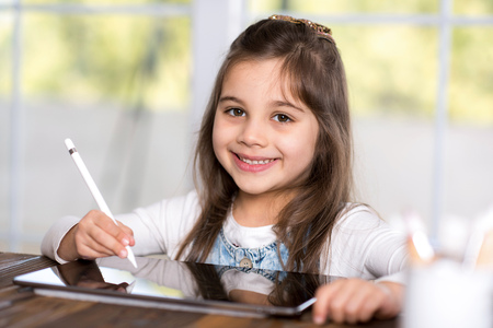Little Girl Drawing Digital Picture On Digital Tablet With Stylus Pen Stock Photo