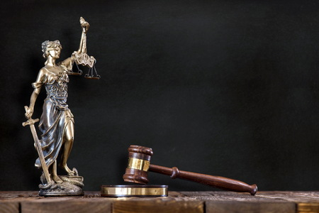 Statue of Lady Justice with Judges Hammer on Black Board Background Stock Photo