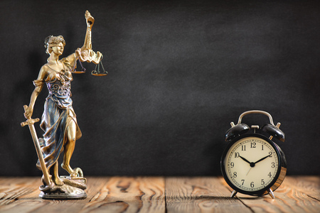 Statue of Lady Justice with Alarm Clock on Black Board Background Stock Photo
