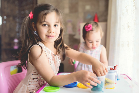 Little Girls Playing With Putty At Home Stock Photo