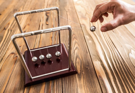 Concept For Action and Reaction or Cause And Result in Business With Newtons Cradle Stock Photo